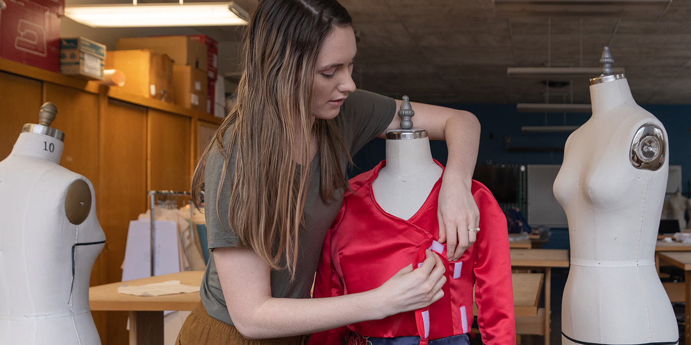 student pinning a dress to mannequin