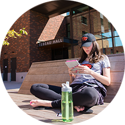 student reading out in front of tebeau hall