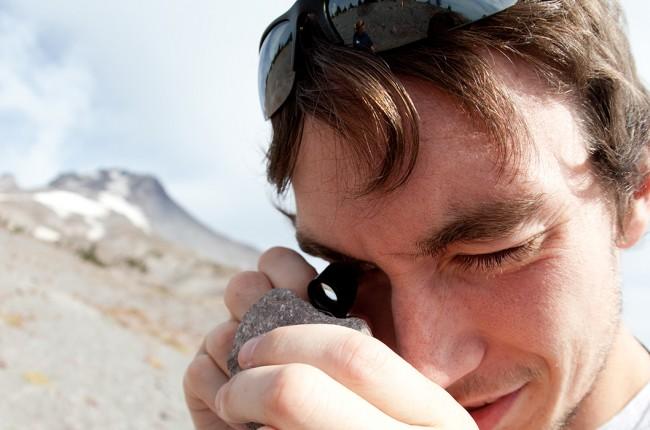 Geology student examining rock on Mt. Hood
