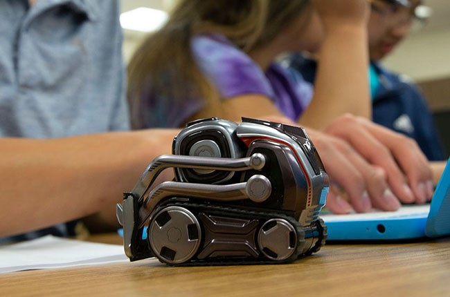 small robot on desk next to student